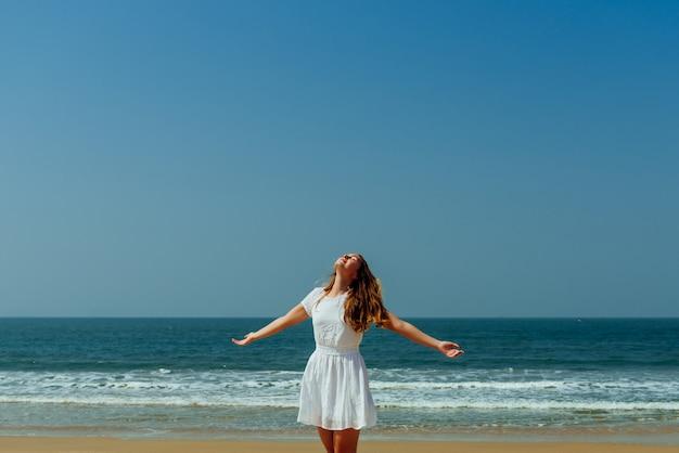 Bella ragazza che gode della vacanza su una spiaggia