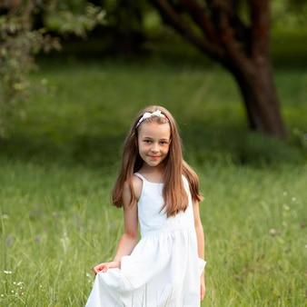 Bella ragazza che indossa un abito bianco