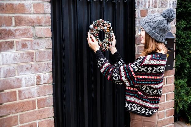 Bella ragazza che indossa un maglione accogliente con ornamento è appeso colorato ghirlanda di natale fatti a mano con coni e palline scintillanti sulla porta all'esterno