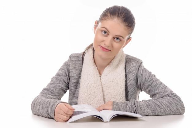 Bella ragazza che legge un libro su fondo bianco