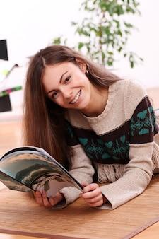 Bella ragazza che legge una rivista