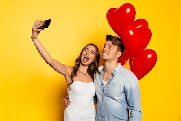 Bella ragazza che mostra una lingua in piedi con il ragazzo che mostra i denti prendendo selfie