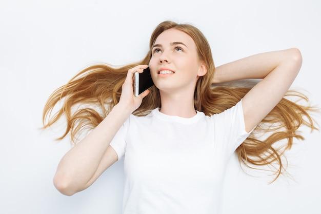 Bella ragazza che parla al telefono, allegro e positivo