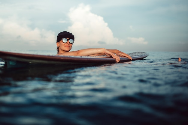 Bella ragazza che posa seduta su una tavola da surf nell'oceano