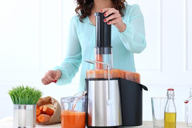 Bella ragazza che produce il succo di carota