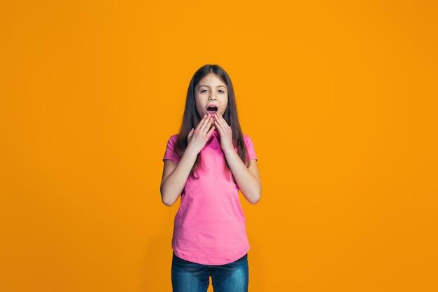 Bella ragazza che sembra sorpresa isolata sulla parete arancione