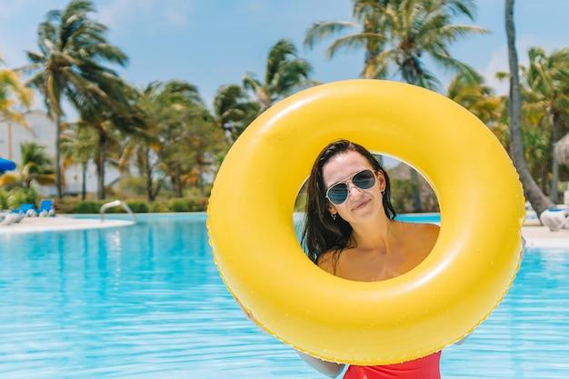 Bella ragazza che si distende nella piscina all'aperto