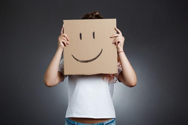 Bella ragazza che si nasconde dietro il cartone con lo smiley sopra la parete grigia.