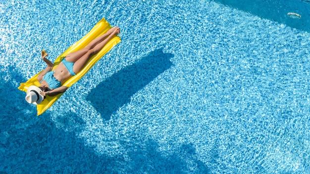Bella ragazza che si rilassa in piscina, nuota sul materasso gonfiabile e si diverte in acqua in vacanza con la famiglia, località di villeggiatura tropicale, vista aerea del drone dall'alto