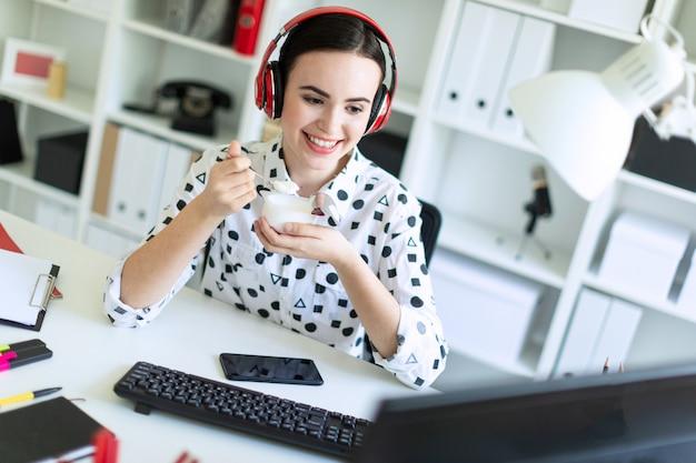 Bella ragazza che si siede in cuffie allo scrittorio in ufficio, mangiando yogurt e guardando il monitor.