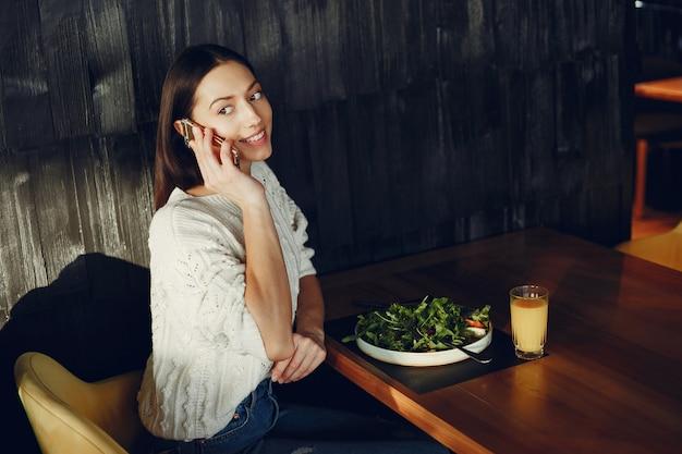Bella ragazza che si siede in un caffè