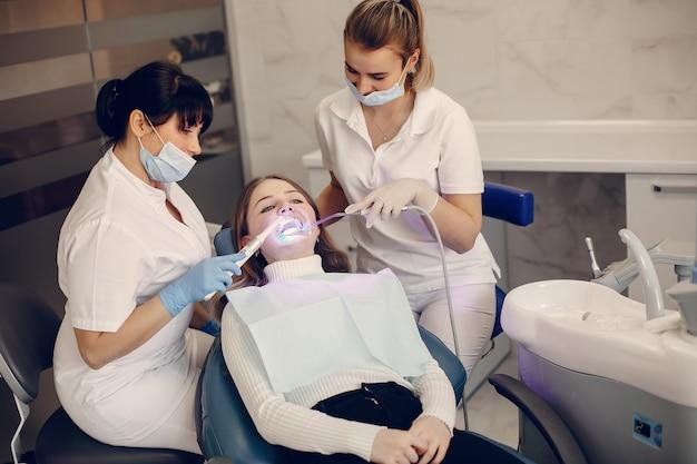 Bella ragazza che si siede nell'ufficio del dentista