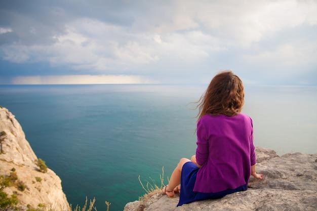 Bella ragazza che si siede sulla roccia e guardando il mare