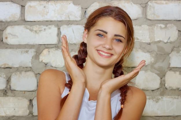 Bella ragazza che sorride con la felicità sul fondo del muro di mattoni
