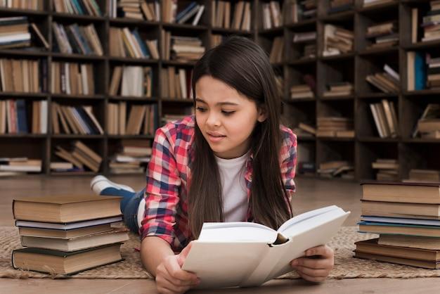 Bella ragazza che studia alla biblioteca
