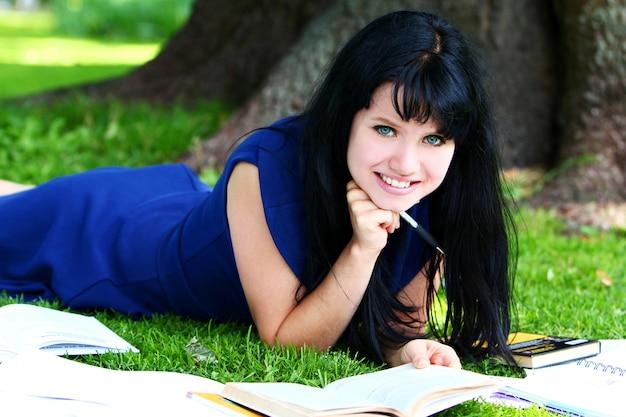 Bella ragazza che studia nel parco