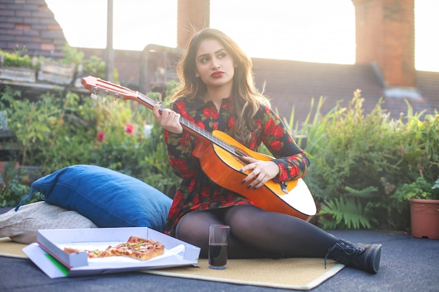 Bella ragazza che suona una chitarra mentre si mangia una pizza
