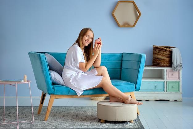 Bella ragazza che tiene la crema per i piedi nelle mani seduto sul divano in abito di seta bianca