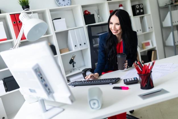 Bella ragazza che tiene un bicchiere in mano con caffè e digitando il testo sulla tastiera, seduto su una sedia in ufficio al tavolo.