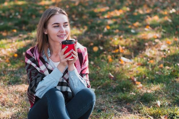 Bella ragazza che tiene una tazza di caffè e distogliere lo sguardo
