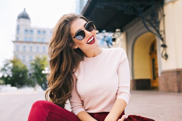 Bella ragazza con acconciatura lunga e labbra vinose divertendosi in città. indossa occhiali da sole e sorride con un sorriso bianco come la neve.