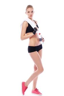 Bella ragazza con asciugamano e bottiglia d'acqua