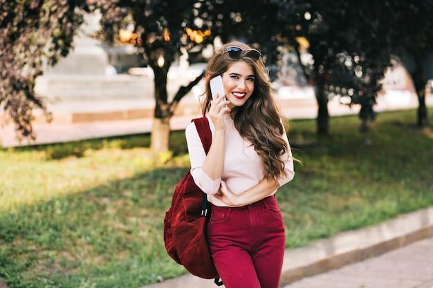 Bella ragazza con capelli lunghi in pantaloni vinosi con borsa sorride nel parco cittadino. sta parlando al telefono e sembra goduta.