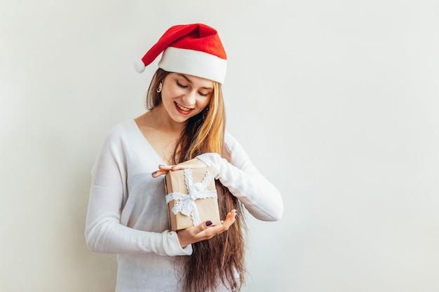 Bella ragazza con capelli lunghi in scatola regalo rosso di babbo natale tenendo confezione regalo isolato su bianco sembra felice ed eccitato.