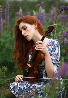 Bella ragazza con capelli rossi e vestito blu che tiene violino sul campo della natura dei fiori.
