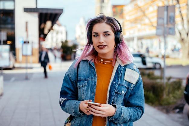 Bella ragazza con capelli tinti ascolto musica in cuffia in via della città.