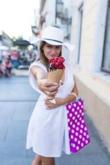 Bella ragazza con cappello bianco e borse per la spesa che mangia il gelato sulla strada della città