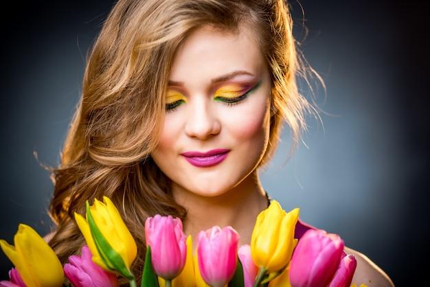 Bella ragazza con fiori di tulipani
