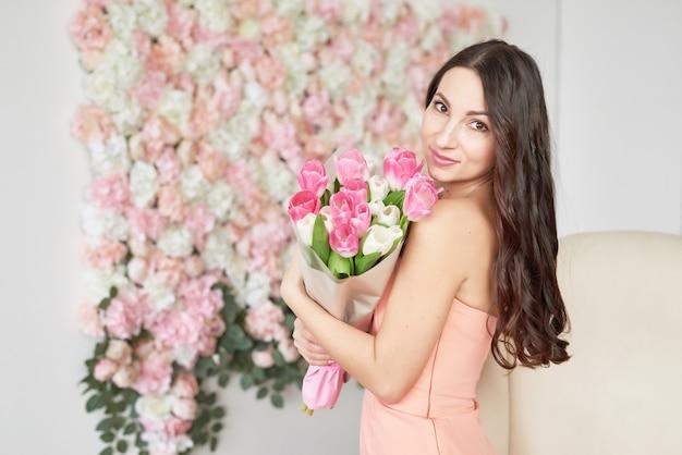 Bella ragazza con fiori di tulipano.