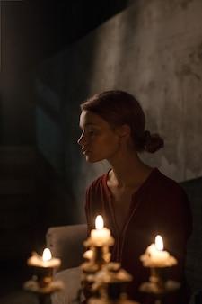 Bella ragazza con gli occhi chiusi in camicia rossa che si siede nella buia stanza buia di fronte a candele nel candelabro