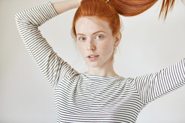 Bella ragazza con gli occhi verdi e le lentiggini sorridenti legando con gioia i suoi lunghi capelli rossi in coda di cavallo
