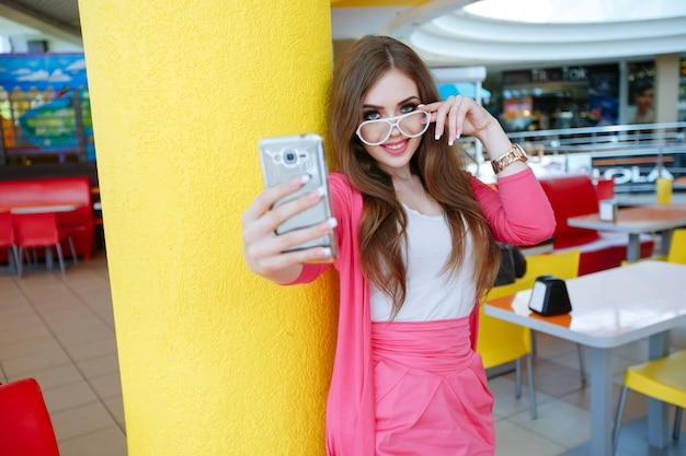 Bella ragazza con gli occhiali bianchi di scattare una foto