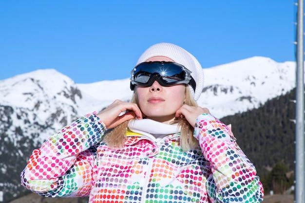 Bella ragazza con gli occhiali scuri nelle montagne innevate