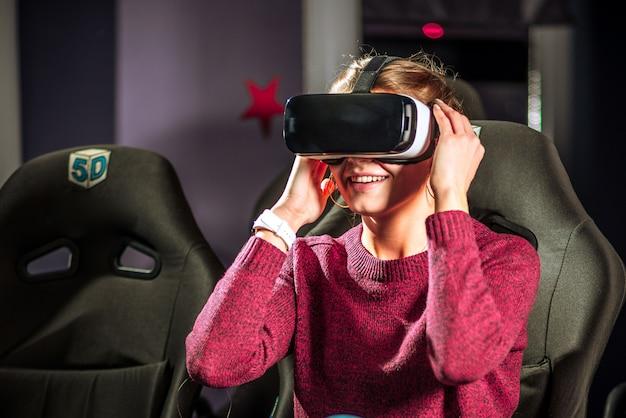 Bella ragazza con gli occhiali virtuali sta guardando un film con effetti speciali