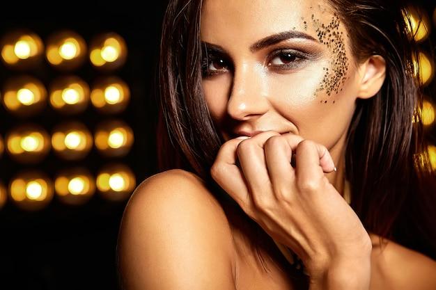 Bella ragazza con glitter dorati sul viso