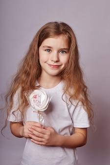 Bella ragazza con i capelli biondi mangia una lecca-lecca