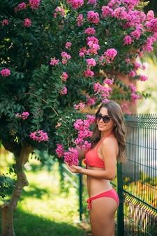 Bella ragazza con i capelli castani in un costume da bagno rosa a prendere il sole in piscina.