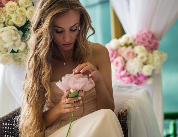 Bella ragazza con i capelli lunghi con fiori veri nelle mani del morbido mistero