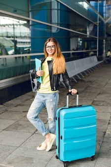 Bella ragazza con i capelli lunghi è in piedi con la valigia fuori in aeroporto. indossa una giacca nera con jeans e tiene il computer portatile. sta sorridendo alla telecamera.