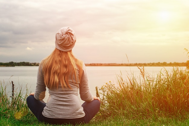 Bella ragazza con i capelli lunghi è seduto sulla riva. vista da dietro tramonto. pace e tranquillità
