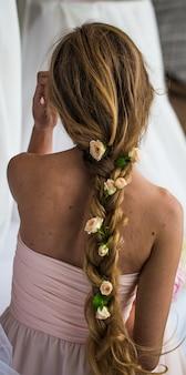 Bella ragazza con i capelli lunghi fiorisce la tenerezza del mistero in una treccia dorso