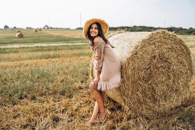 Bella ragazza con i capelli lunghi in occhiali da sole e cappello di paglia in posa su un campo di grano vicino a balle di fieno. felice bruna in abito estivo