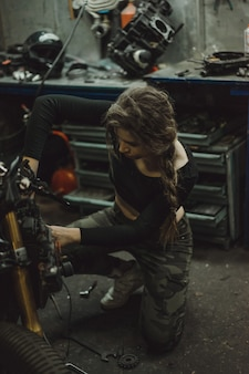 Bella ragazza con i capelli lunghi nel garage di riparare una moto
