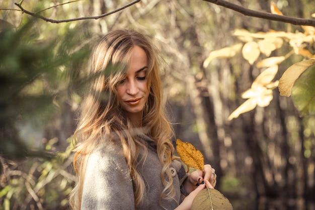 Bella ragazza con i capelli lunghi nella foresta di autunno, concetto di stagione autunnale