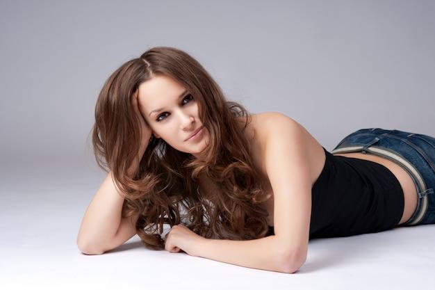 Bella ragazza con i capelli lunghi, sdraiato sul pavimento