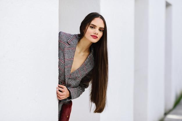 Bella ragazza con i capelli molto lunghi che indossa cappotto invernale e berretto all'aperto.